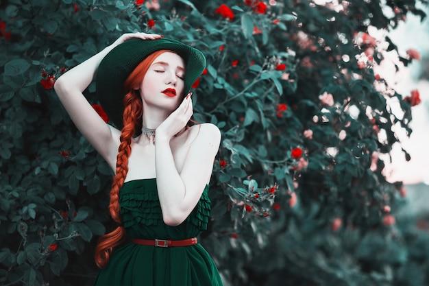 Das rothaarige mädchen in einem langen kleid und einem grünen vintage-hut, der vor einem hintergrund von pfirsichrosen aufwirft. romantische dame mit rotem zopf und roten lippen im stil der aufklärung. blumengarten