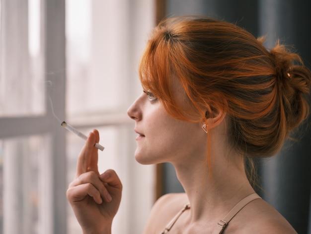 Das rothaarige mädchen raucht eine zigarette