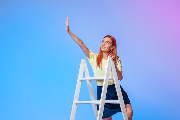Das rothaarige mädchen steht oben auf der treppe und streckt ihre hand an einer rosa-blauen wand aus