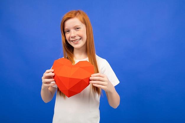 Das rothaarige teenager-mädchen erhielt ein geschenk in form eines herzens auf einem blauen studiohintergrund.