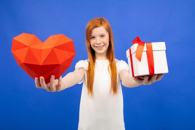 Das rothaarige teenager-mädchen hält eine blaue geschenkbox hoch