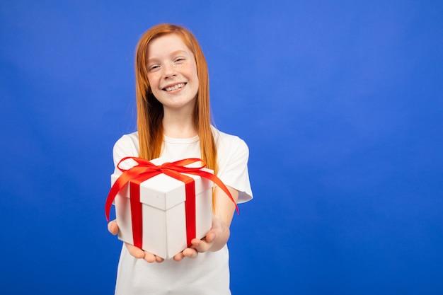 Das rothaarige teenager-mädchen hält eine blaue geschenkbox mit kopienraum aus