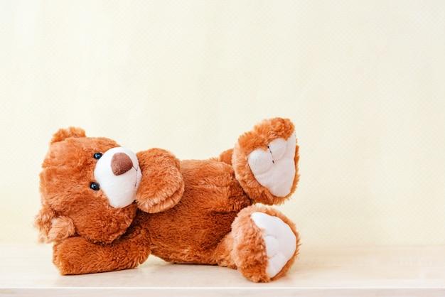 Das ruhende stofftier teddybär liegt auf der seite im kinderzimmer und träumt