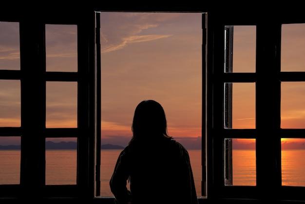 Das schattenbild einer jungen frau, die sonnenuntergang das fenster mit seeansichten schaut.
