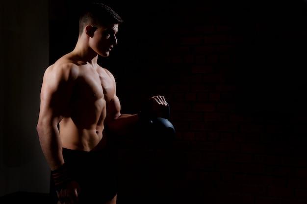 Das schattenbild eines jungen mannes, der gewicht tut, trainiert mit einem dummkopf