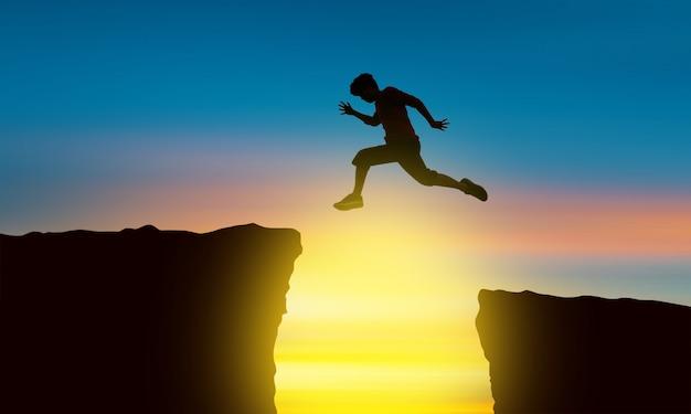 Das schattenbild eines mannes, der über den abgrund zum zeitpunkt des sonnensatzes, des konzeptes des sieges und des erfolgs springt