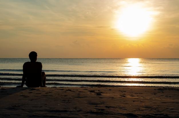 Das schattenbildfoto eines mannes, der alleine auf dem strand sitzt, genießen sonnenaufgangmoment.
