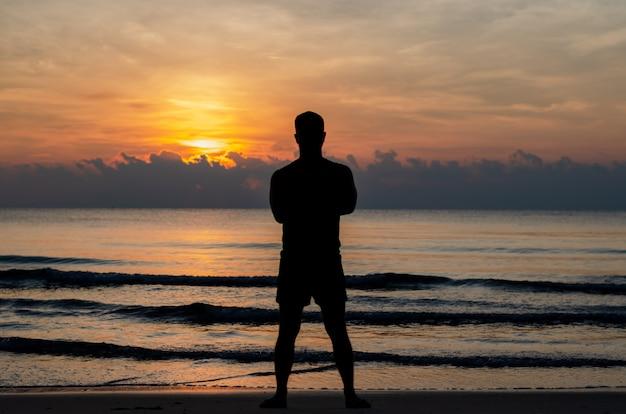 Das schattenbildfoto eines mannes, der alleine auf dem strand steht, genießen sonnenaufgangmoment.