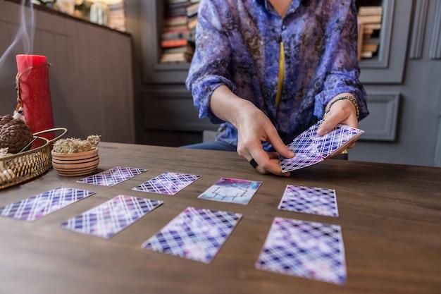 Das schicksal sehen. nahaufnahme von tarotkarten in weiblichen händen während einer wahrsagerei
