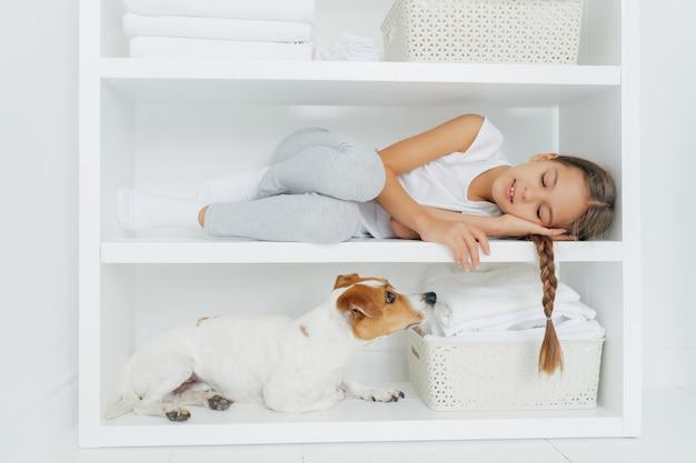 Das schläfrige kleine mädchen fühlt sich wohl, als es auf dem weißen regal liegt, das in der freizeitkleidung gekleidet ist, die nach dem waschen ihres hundes müde ist