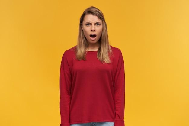 Das schockierte, unzufriedene blonde mädchen sieht empört aus, der mund weit geöffnet, vor empörung erstarrt und trägt einen lässigen roten pullover
