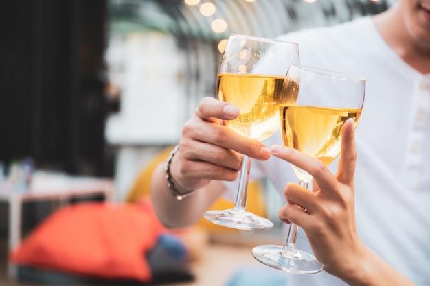 Das schöne asiatische junge paar genießt es, gemeinsam weißwein auf der valentinstagsparty in der bar auf dem dach und im restaurant des 5-sterne-hotels zu jubeln. romantisches asienpaar, das am valentinstag zusammen feiert