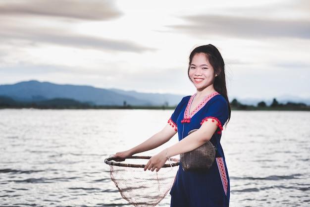 Das schöne asiatische mädchen, das fischfalle und korb hält, bereiten vor sich, die fische zu fangen, die auf dem gebiet nahe see an der landschaft von thailand gehen