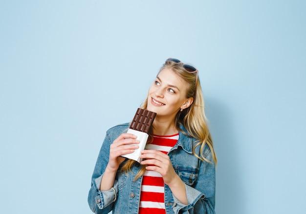 Das schöne blonde mädchen, das schokolade isst, ist auf einem blauen hintergrund aufgeregt