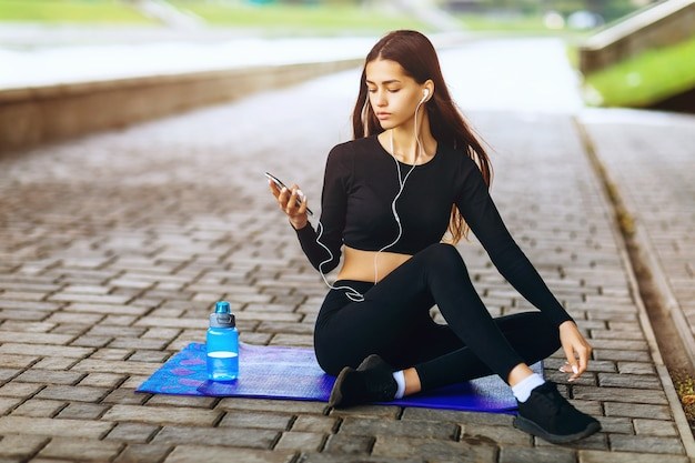 Das schöne braunhaarige mädchen hört musik, während es auf einer turnmatte sitzt, und ruht sich nach dem sport aus