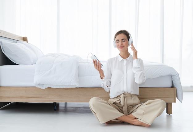 Das schöne entspannende hören der jungen frau musik mit kopfhörern schließen vom smartphonesetting am schlafzimmer an