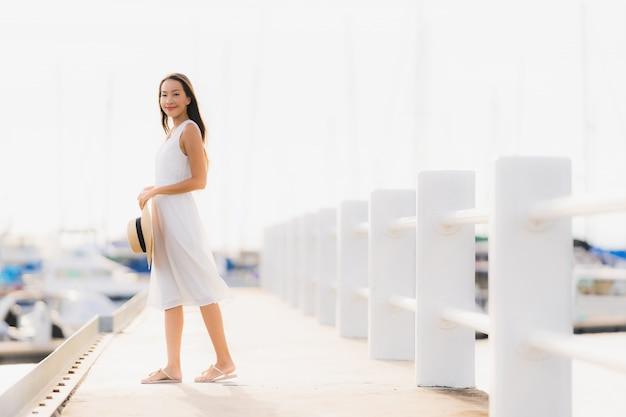 Das schöne junge asiatische frauenfreizeitlächeln des porträts, das glücklich ist, entspannen sich um yachthafen