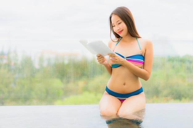 Das schöne junge asiatische frauenlächeln des porträts, das glücklich ist, entspannen sich mit lesebuch um swimmingpool im hotelerholungsort für freizeit