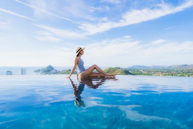 Das schöne junge asiatische frauenlächeln des porträts, das glücklich ist, entspannen sich um swimmingpool im hotelerholungsort für freizeit