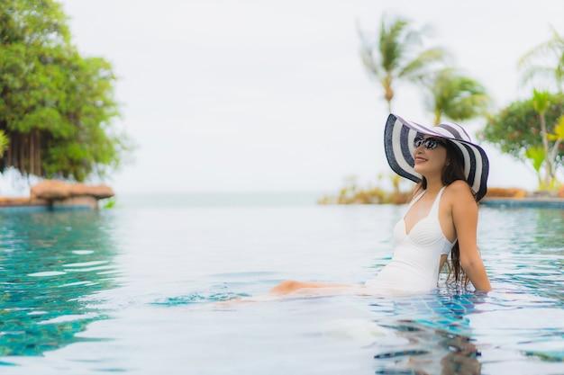 Das schöne junge asiatische frauenlächeln des porträts, das glücklich ist, entspannen sich um swimmingpool im hotelerholungsort