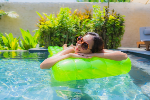 Das schöne junge asiatische frauenlächeln des porträts, das glücklich ist, entspannen sich und freizeit im swimmingpool