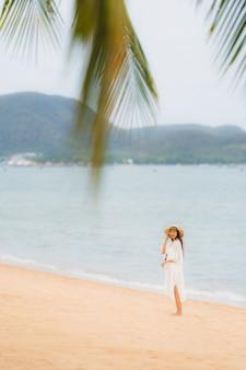 Das schöne junge asiatische glückliche frauenlächeln des porträts entspannen sich auf dem strandseeozean