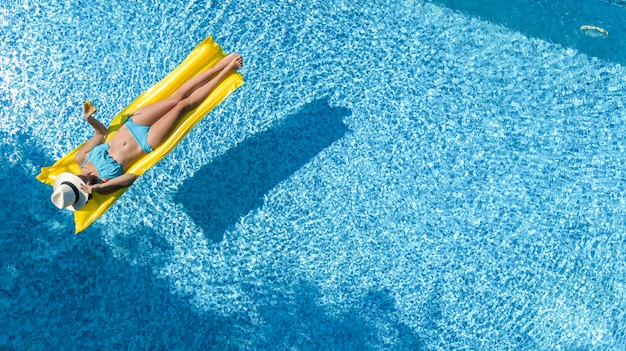 Das schöne junge mädchen, das im swimmingpool sich entspannt, schwimmt auf aufblasbarer matratze und hat spaß im wasser auf familienurlaub, tropisches ferienzentrum, luftbrummenansicht von oben