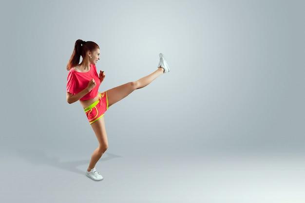 Das schöne, junge mädchen schlägt einen fuß, treibt sport. das konzept der gewichtsabnahme, sporttraining, ernährung, gesunde ernährung