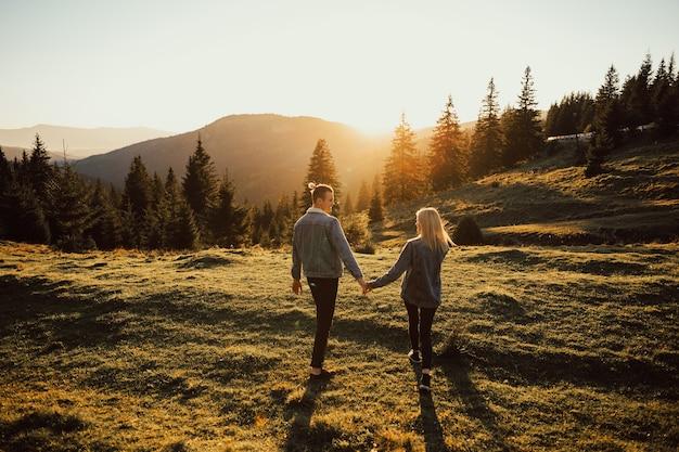 Das schöne junge paar genießt die natur am berggipfel.
