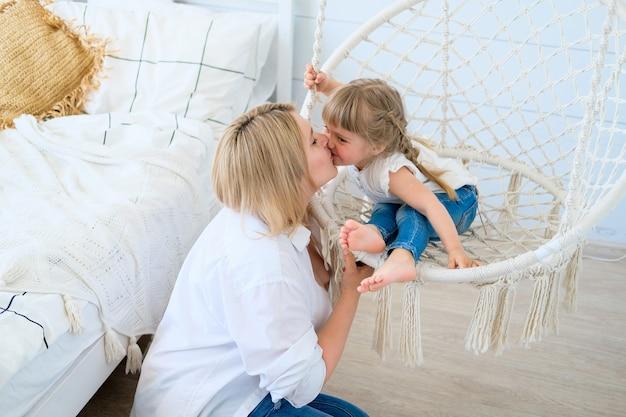 Das schöne kleine mädchen, das in einem hängenden stuhl im schlafzimmer mit ihrer mutter baby schwingt, küsst mama