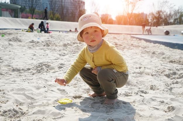 Das schöne kleine mädchen spielt am strand