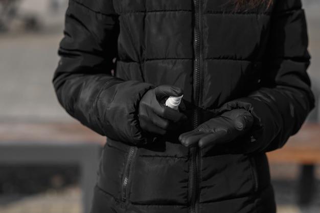 Das schöne mädchen bleibt mit einer gesundheitsmaske gegen covid-19, coronavirus, hinter dem tisch, sprüht desinfektionsflüssigkeit auf op-handschuhe und wartet auf passagiere am flughafen belgrad