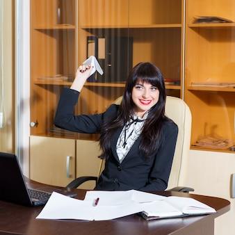 Das schöne mädchen, das am schreibtisch im büro sitzt und startet ein papierflugzeug