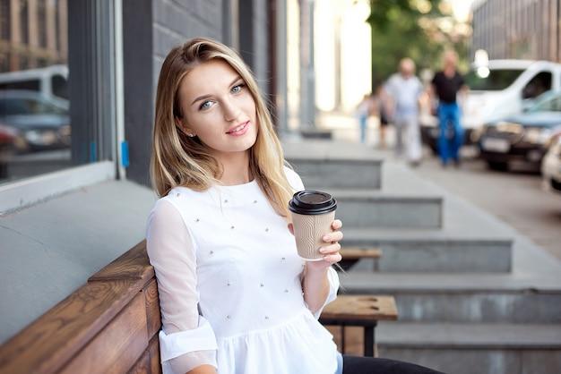 Das schöne mädchen, das in die stadt geht und trinkt, nimmt kaffee durch ein café im freien weg. stadtmorgenszene.