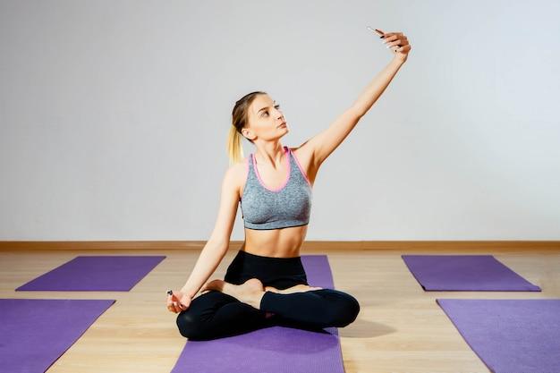 Das schöne mädchen, das yoga tut, macht selfie auf smartphone