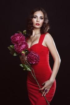 Das schöne mädchen in einem langen roten kleid hält eine exotische blume