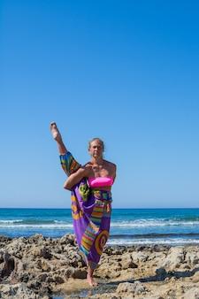 Das schöne mädchen mit einer sportfigur praktiziert yoga im freien in der nähe des meeres. sommer.