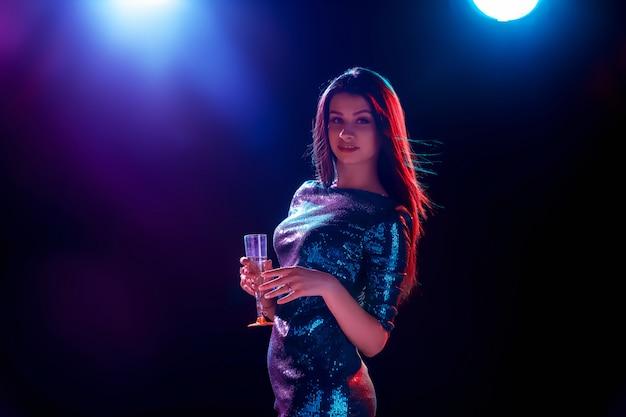 Das schöne mädchen tanzt auf der party champagner trinkend