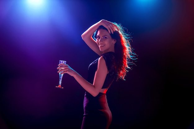 Das schöne mädchen tanzt auf der party und trinkt champagner