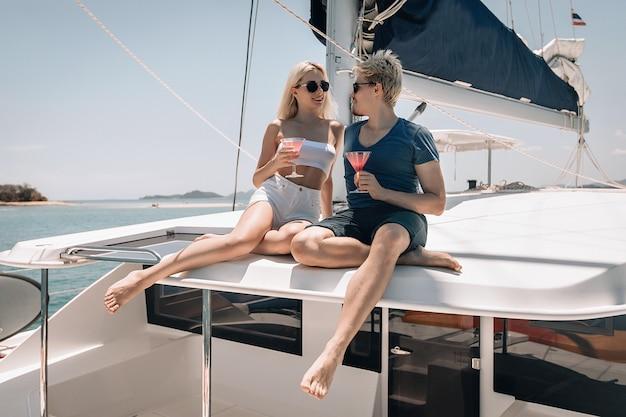Das schöne paar sitzt auf dem dach ihrer großen weißen laxury-yacht, schaut sich an und trinkt einen cocktail.