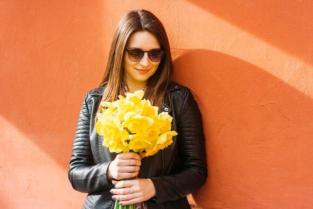 Das schöne porträt der brunettefrau gelben frühling halten blüht am sonnigen tag