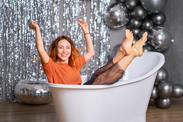 Das schöne rothaarige mädchen freut sich, gekleidet in der badewanne zu sitzen. vor dem hintergrund von lametta und luftballons. erfolgskonzept.