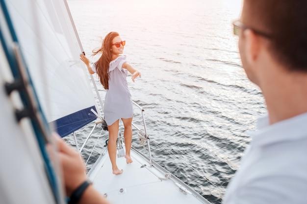 Das schöne und gut gebaute modell steht am bug der yacht und hält sich an der röhre fest. sie sieht ihren freund hinter sich an. brünette versucht ihn mit der hand zu erreichen und lächelt.