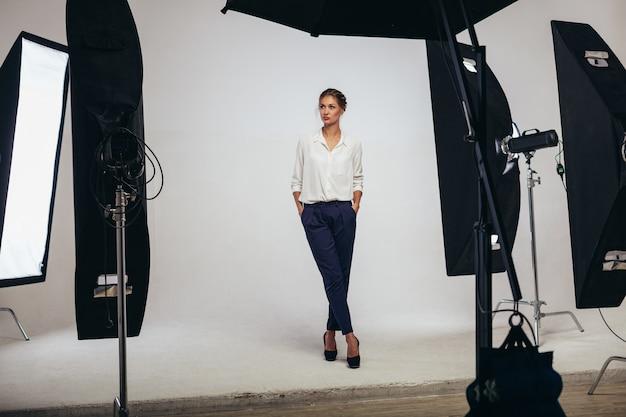 Das schöne weibliche frauenmodell des geschäfts, das am studio im licht aufwirft, blinkt