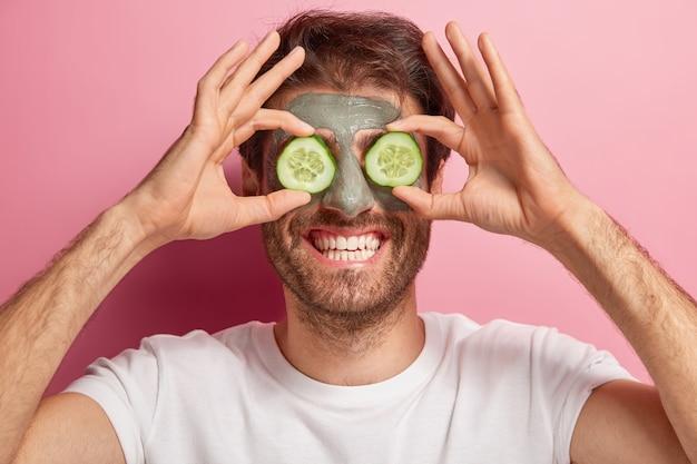 Das schönheitsporträt des fröhlichen mannes stellt mit tonmaske auf gesicht, zwei gurkenscheiben auf augen auf, trägt weißes t-shirt, hat zahniges lächeln und borsten