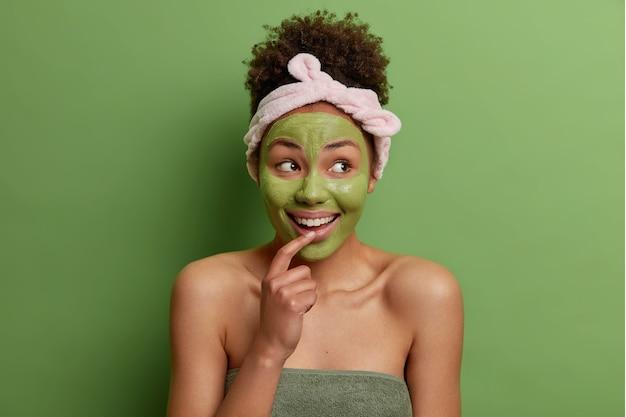 Das schönheitsporträt des glücklichen weiblichen modells trägt grüne pflegende maske auf gesicht auf