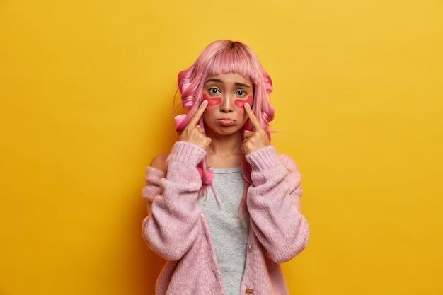 Das schönheitsporträt des traurigen mädchens zeigt auf kosmetische kollagenflecken unter den augen, hat düsteren ausdruck, hat rosa haare mit fransen, trägt lockenwickler