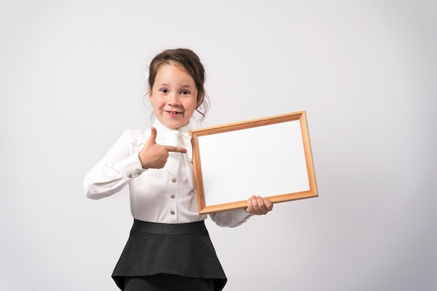 Das schulmädchen der ersten klasse hält ein weißes blatt für die inschrift