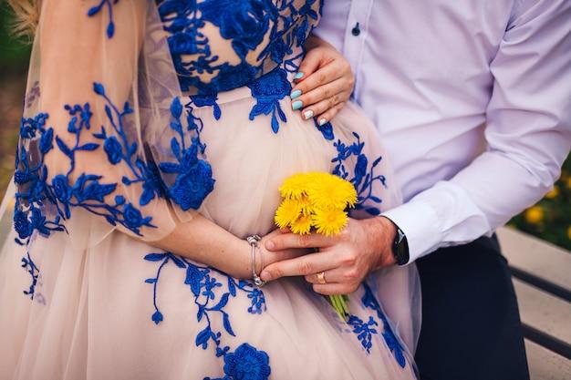 Das schwangere mädchen sitzt auf dem schoß des jungen und hält gelbe blumen in den händen