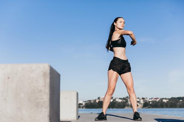 Das schwarz gekleidete sportmädchen wärmt sich morgens vor dem laufen auf dem spielplatz am stadtstrand auf